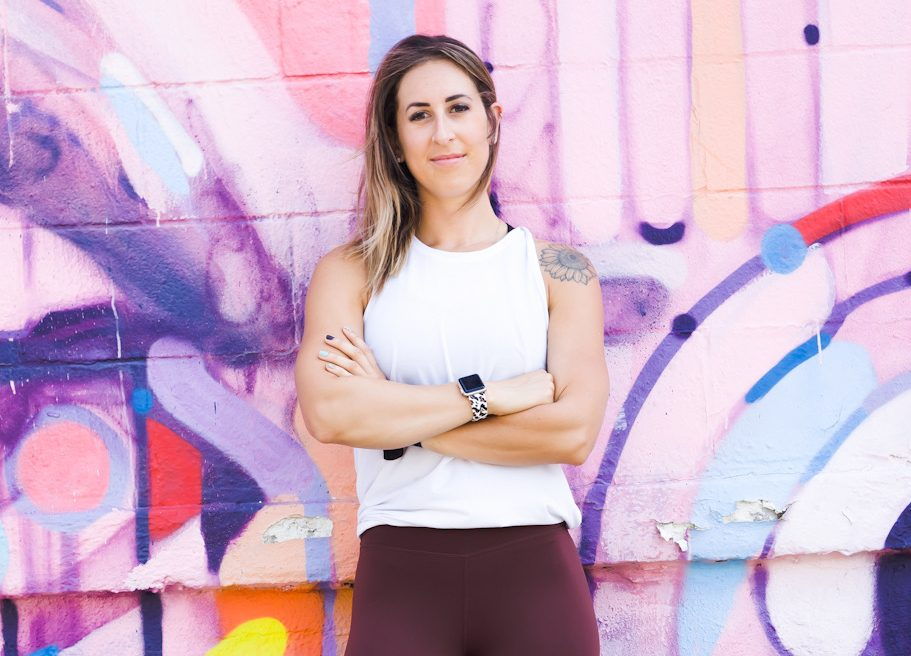 Heather in front of a pink and purple graffiti wall with her arms crossed.